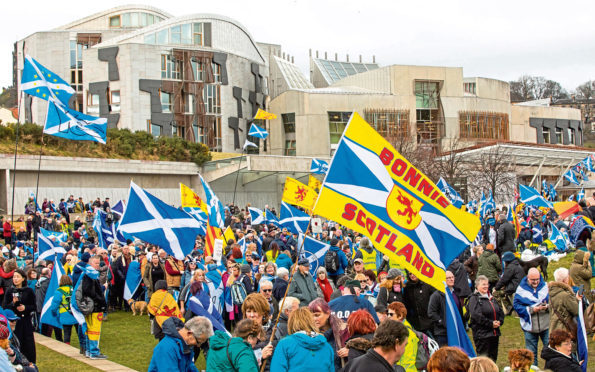 Thousands of people join Hands off our Parliament (HOOP) demo at Scottish Parliament. The demonstration surrounded Holyrood with a living chain of hands. March 23 2018