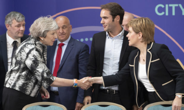 Prime Minister Theresa May and First Minister Nicola Sturgeon shake hands after signing the Edinburgh and South East Scotland City Region Deal at the University of Edinburgh,