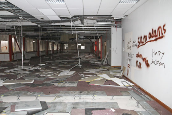 Vandals have torn down the building's ceiling tiles and smashed windows