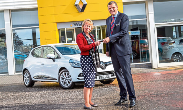 A customer receives the kes to their new car at an Arnold Clark dealership