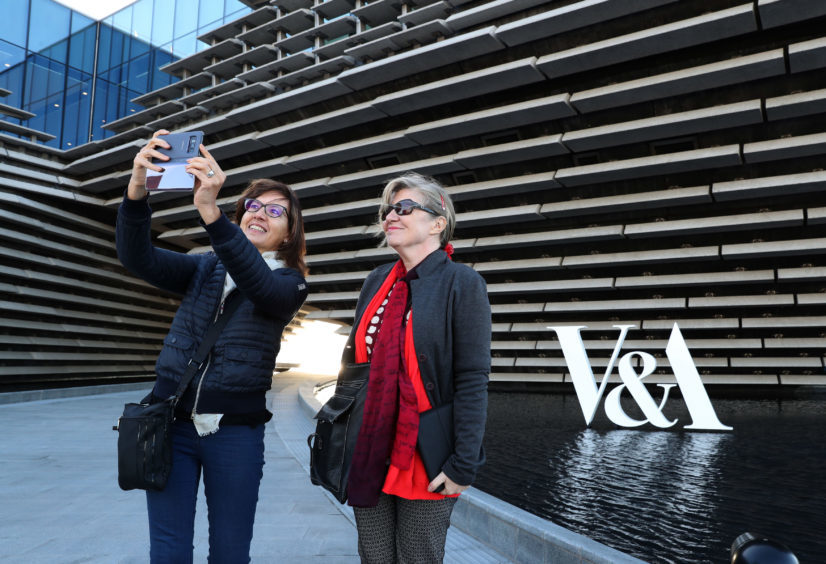 Two women take a selfie outside the finished exterior of the new eighty million pound V&A Dundee museum.