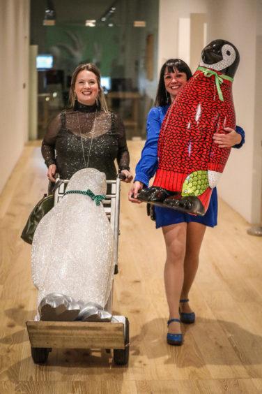 Artists Joanne MacFadyen and Suzanne Scott moving penguins.