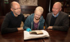 The Ackermann booklet being viewed by (left to right) Paul Adair, Margaret Borland-Stroyan and Roben Antoniewicz.