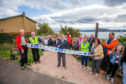 The ribbon cutting was performed by Colin McPhail (former chair of Dalgety Bay Community Council). On the left is (left to right) Dick Alderson (Committee Member of Dalgety Bay Community Woodlands Group) and David MacLeod (Chair of Dalgety Bay Community Woodlands Group). On the right with high-vis is Kathryn Green (Secretary of Dalgety Bay Community Woodlands Group).