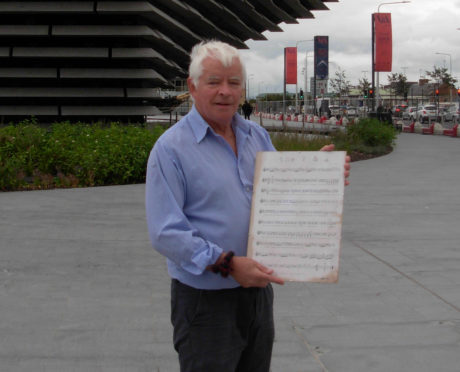 Eddie Cairney with a copy of his song in front of the V&A Dundee