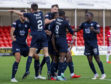 The Dundee players celebrate Kharl Madianga's goal.