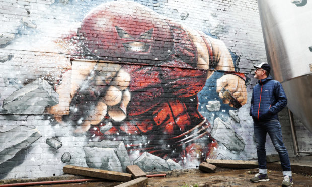 71 Brewing's Duncan Alexander with the Juggernaut mural.