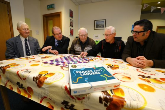 Veterans Minister Graeme Dey MSP, 2nd left, playing a specially adapted game of snakes and ladders for veterans, during his visit to the Dementia Hub, with L/R, Ian Bruce, John Duncan, James Wallace and Graham Galloway - Kirrie Connections