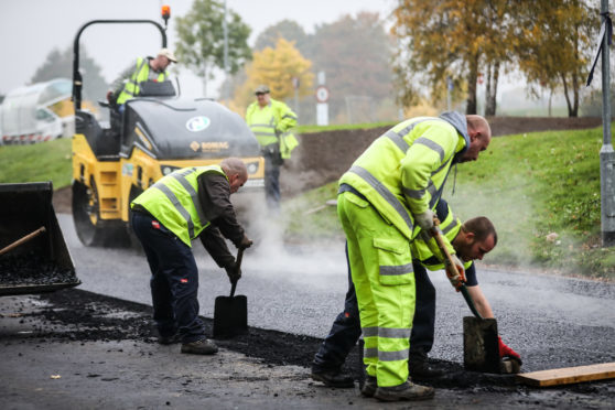 Workmen laying the road that contains plastic mixed with bitumen.