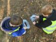 Children learning in woodland surroundings.