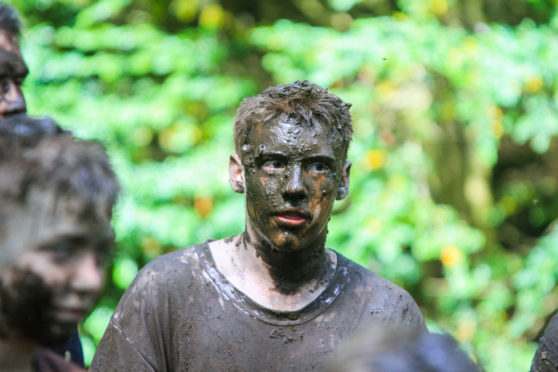 A Scout taking part in the mud ritual at the Blair Atholl Jamborette, an international scouting event.