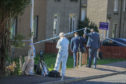 Detectives arrive at the flat in Rintoul Avenue.