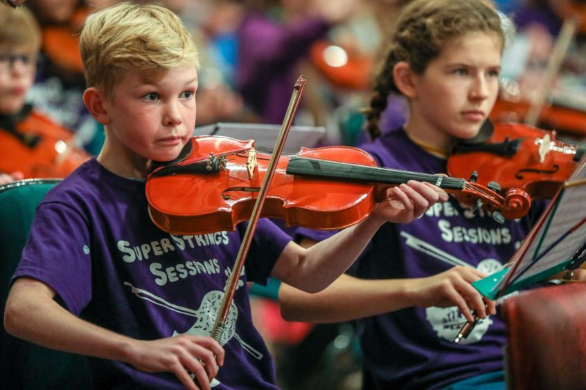 Youngsters from the Super String Orchestra performing.