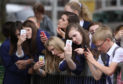 School children on mobile phones trying to get a picture of a statue unveiling in 2014.