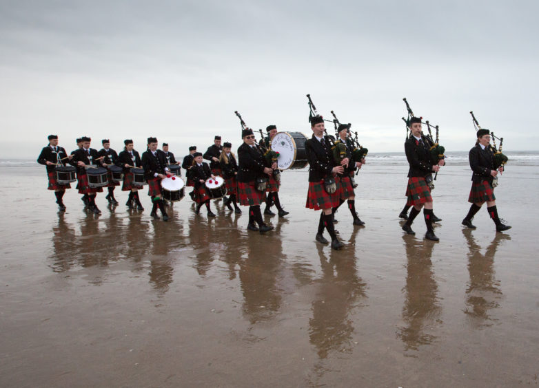 A pipe band at West Sands Beach, St Andrews.