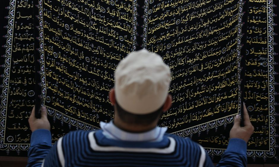 A man inspects the world's first Quran entirely in embroidery art, which was made by Syrian artist Mohammad Ma in Bursa, Turkey. Ali Atmaca/Getty Images