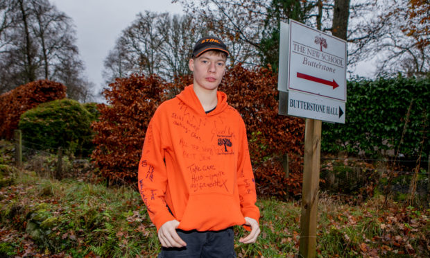 Former Butterstone pupil Duncan Fairlie, aged 16, pupil, with his school top signed by classmates.