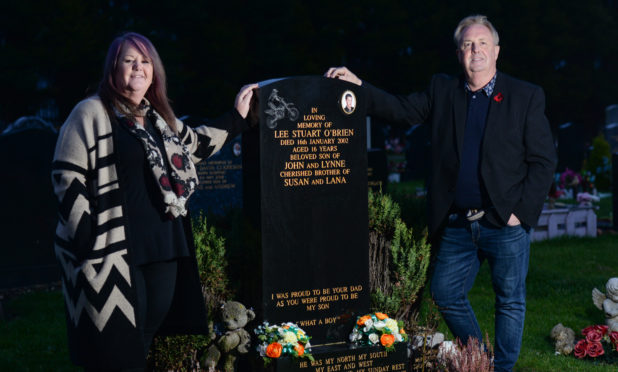 Councillor John O'Brien and his sister Katy Ovenstone beside John's son's grave.