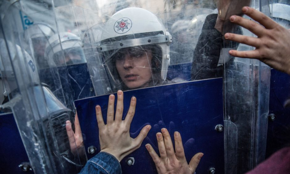 A Turkish female riot police officer reacts during clashes with women's rights activists as they try to march to Taksim Square to protest against gender violence in Istanbul.  Bulent Kilic/Getty Images