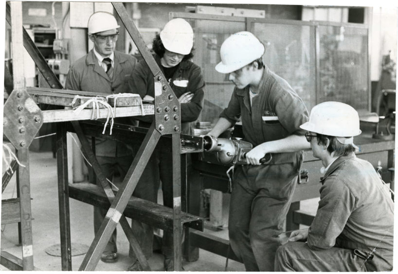 Technical instructor Mr Dave Adam with (from left) 12-year-old apprentices Sandy McIntosh, Garry McLeish, both from Dundee, and Brett Doward from Michelin's Aberdeen plant. Date: 22/04/1982.