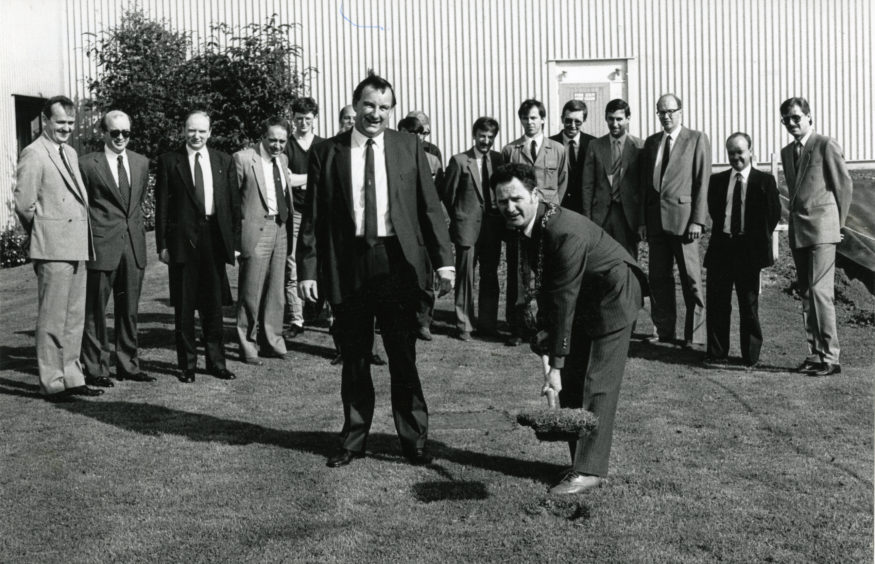 Lord Provost Tom Mitchell cuts the first sod at the Michelin Warehouse, watched by Mr Fraser Kyle, factory manager and other guests. Date: 19/8/87.