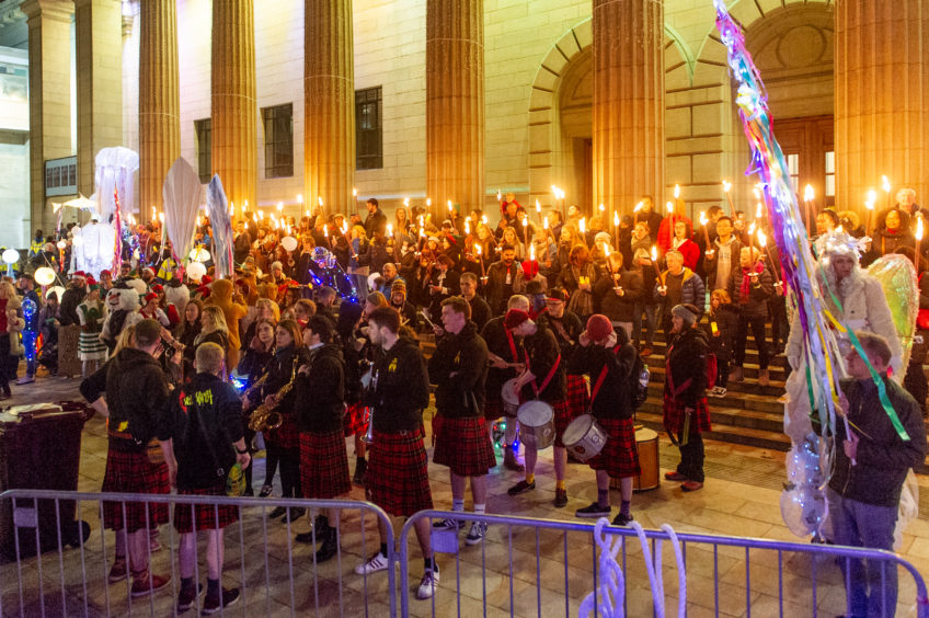 The torch-lit procession arrives and lines up on the Caird Hall steps.
