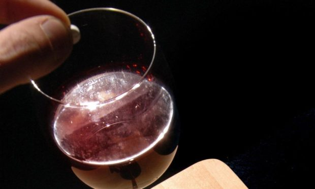 Posed photograph of a glass of wine being spiked.