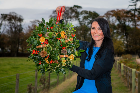 Gayle shows off the stunning festive wreath she made at Balgove Larder.