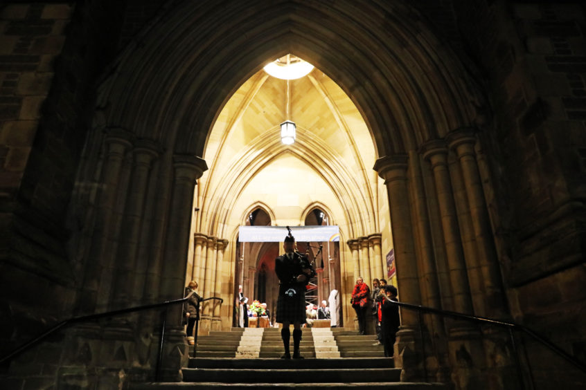 Piper Neil Nicholson at the doorway to St Paul's Cathedral., Dundee.
