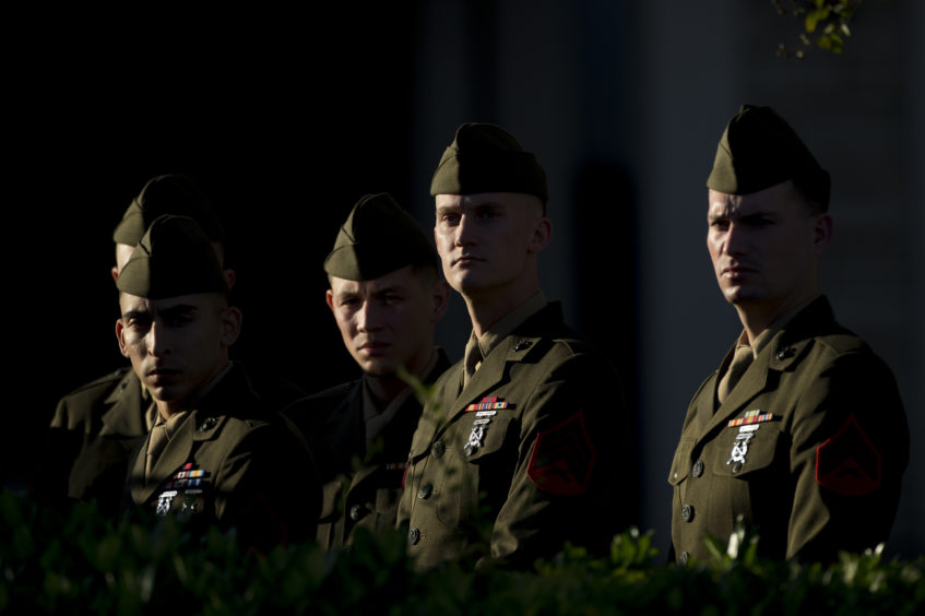 Members of the U.S. Marine Corps in their dress greens stand outside where the remains of President George H.W. Bush are kept before the first departure ceremony.