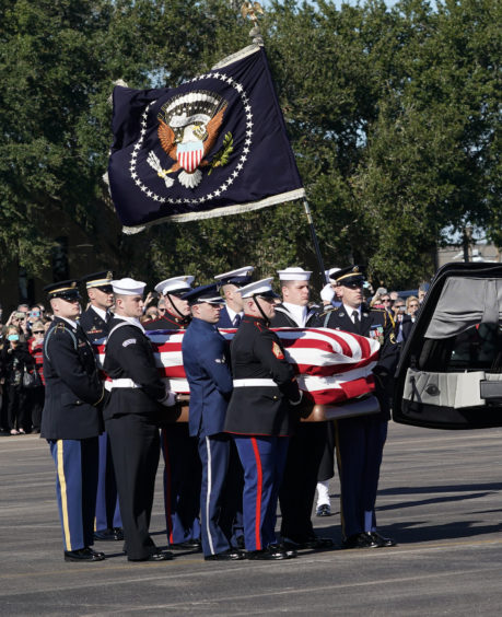 Joint services military honor guard carry the flag-draped casket of the remains of President George H.W. Bush during a departure ceremony to Washington D. C at Ellington Field
