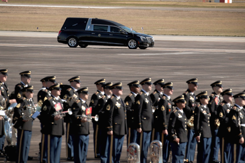The remains of President George H.W. Bush are loaded onto Special Air Mission 41 by a military honor guard before flying to Washington D. C.