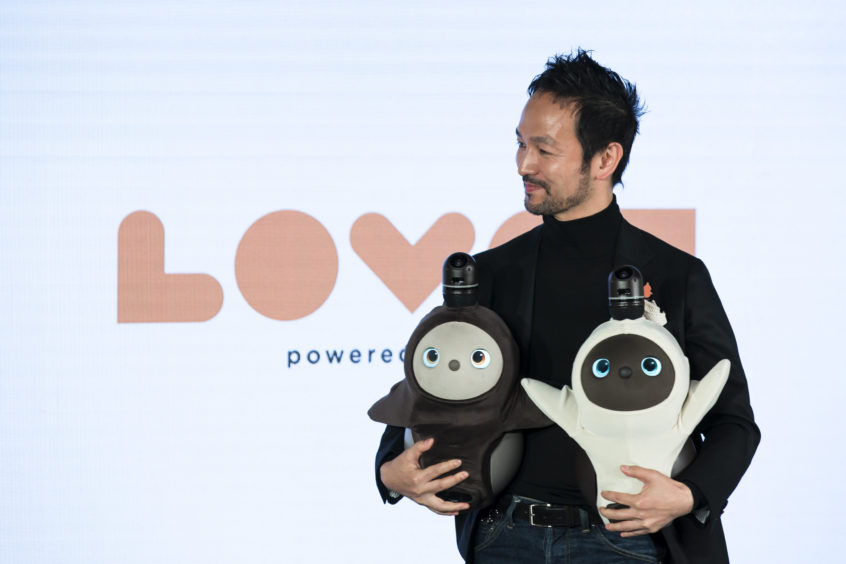Groove X Inc. Founder and Chief Executive Officer Kaname Hayashi holds a pair of Lovot robots during the unveiling event.