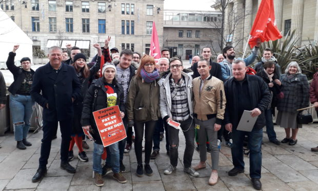 "Union members and former Brassica employees celebrate their ""small victory"" outside the City Chambers on Thursday."