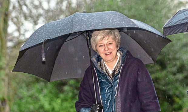 Prime Minister Theresa May shelters from the rain