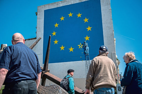 People view a mural by British graffiti artist Banksy, depicting a workman chipping away at one of the stars on a European Union (EU) themed flag on May 9, 2017 in Dover, England.