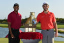 Spain's Jon Rahm, right, poses with host Tiger Woods after winning the Hero World Challenge.