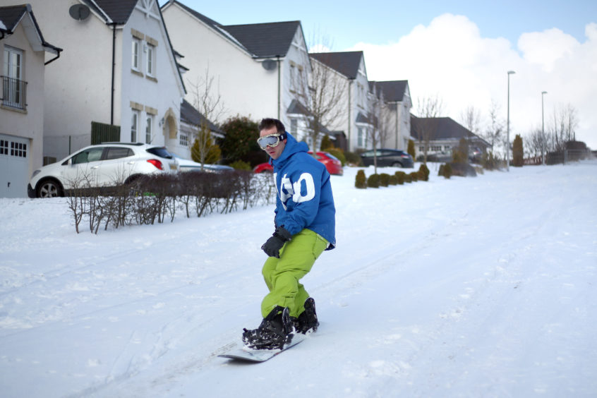 Snow boarder Kevin Trueland had no problems on Balmossie Road in the deep snow. Kris Miller/DCT Media