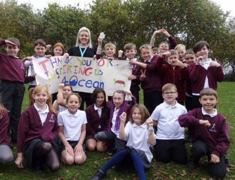 Northmuir P5 teacher Nikki Paterson with pupils and the 4Ocean bracelets they received