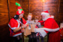 Gayle aka a sort of elf, helps Santa hand over pressies to sister Niamh (9) and Alannah (4) Cullen.
