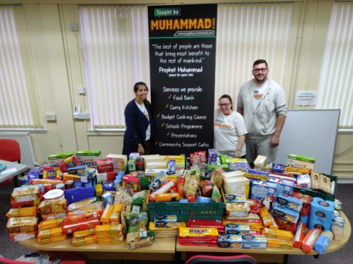 TBM's Amna Nawaz-Ali with volunteers Claire Leslie and Kairne Leslie alongside the 260kg of food