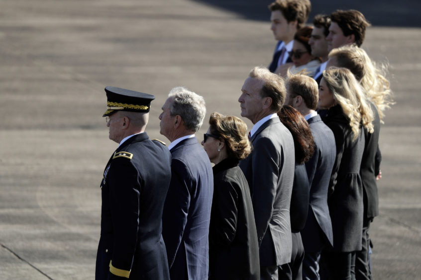 Family members of former President George H.W. Bush, including former President George W. Bush, second from left, watch as members of the military carry the casket to Special Air Mission 41at Ellington Field during a departure ceremony for a state funeral,2018. President George H.W. Bush died last week in Maine. The painting was done by his son and former 43rd President George W. Bush.