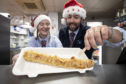 Chelsea McGowan and chip-shop owner Scott Davie serve up a deep-fried pig-in-blanket.