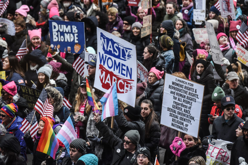 A large crowd marches down 6th Ave. while participating in New York's Women's March.