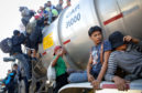 People from a caravan of Central American migrants climb onto a tanker truck they were hoping to catch a ride from, on their way toward the United States, .Some members of the caravan are in Mexico while others are further behind in Guatemala.