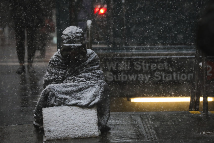 A homeless man sits in the falling snow in the Financial District  in New York City. The frigid air from the polar vortex in the Midwest will expand into the New York over the next few days. The city is under a wind chill advisory through Thursday morning, with possible win gusts up to 50 miles per hour.