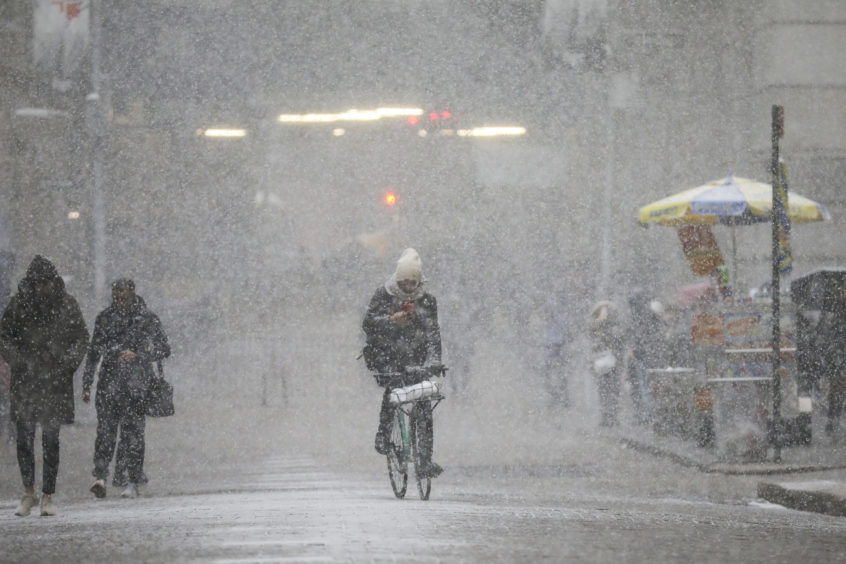 A cyclist rides through the falling snow in the Financial District in New York City. The frigid air from the polar vortex in the Midwest will expand into the New York over the next few days. The city is under a wind chill advisory through Thursday morning, with possible win gusts up to 50 miles per hour.