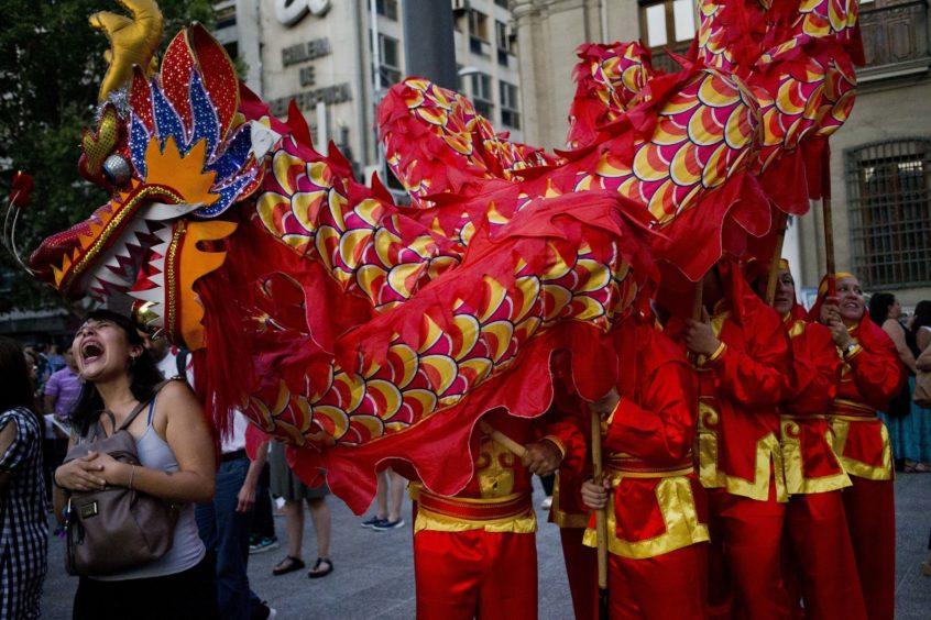 A woman enjoys the dragon dancer presentation.