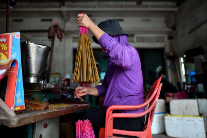 Preparing incense sticks at a workshop.