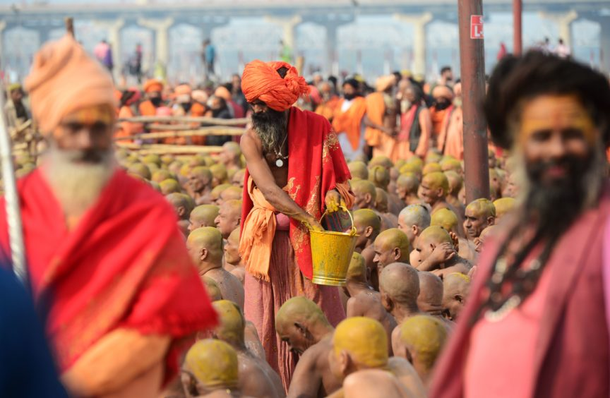 Newly initiated 'Naga Sadhus' (Hindu holy men) sit as they perform rituals on the banks of the Ganges River during the Kumbh mela festival, in Allahabad.